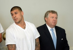 New England Patriots former tight end Aaron Hernandez (left) stands with his attorney Michael Fee as he is arraigned in Attleboro District Court. Hernandez is charged with first degree murder in the death of Odin Lloyd. Mandatory Credit: The Sun Chronicle/Pool Photo via USA TODAY Sports