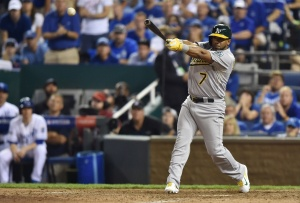 Oakland Athletics second baseman Alberto Callaspo (7) hits an RBI single against the Kansas City Royals during the twelfth inning of the 2014 American League Wild Card playoff baseball game at Kauffman Stadium. The Royals won 9-8. Mandatory Credit: Peter G. Aiken-USA TODAY Sports