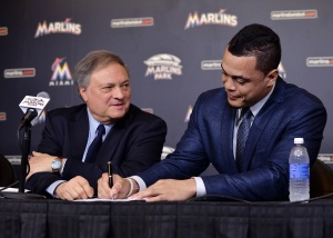 Miami Marlins right fielder Giancarlo Stanton (right) signs his contract next to Marlins owner Jeffery Loria (left) during a press conference at Marlins Park. Mandatory Credit: Steve Mitchell-USA TODAY Sports